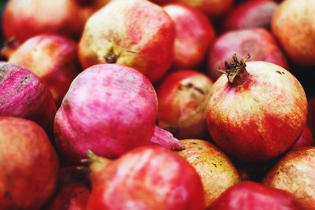 Stapel granaatappels verkocht op de fruitmarkt, voedselachtergrond