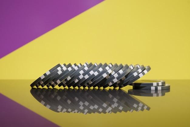 Stapel grijze casinofiches op een kleurrijke achtergrond