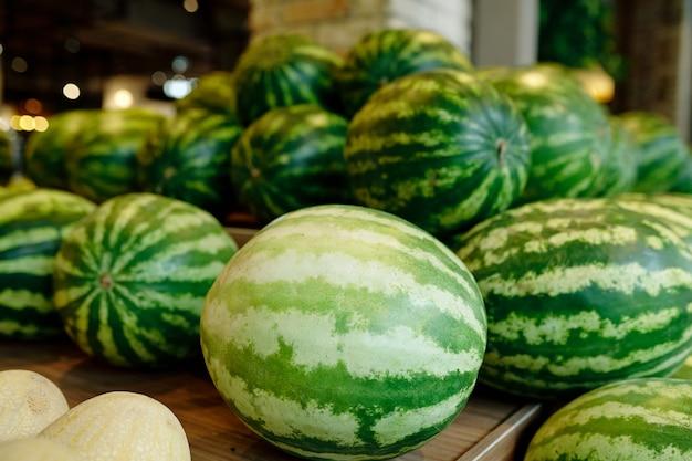 Stapel groene grote watermeloenen die op houten vertoning binnen eigentijdse supermarkt liggen