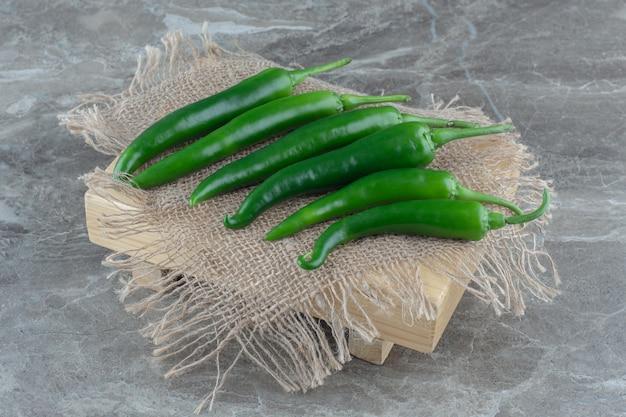 Stapel groene hit chili pepers en zak over grijs oppervlak