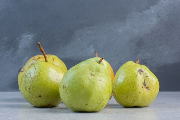 Stapel groene peren op grijze achtergrond.