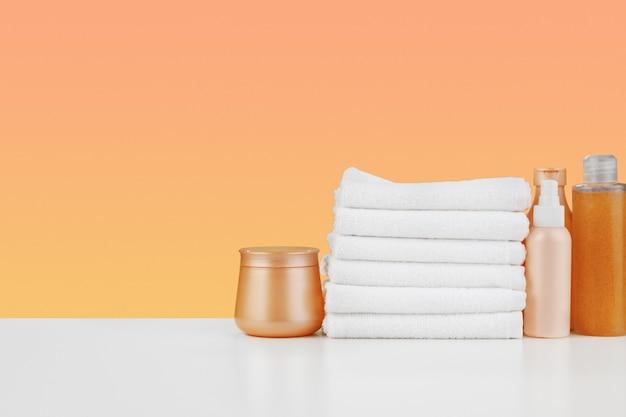Stapel handdoekenflessen met shampoo op witte tafel