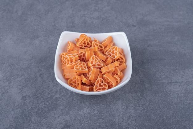 Stapel hartvormige pasta in witte kom.