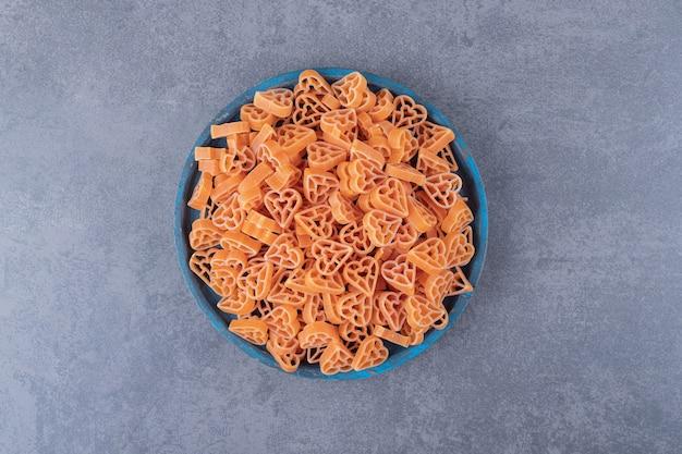 Stapel hartvormige pasta op blauw bord.
