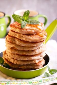 Stapel haver pannenkoeken met stroop in een pan
