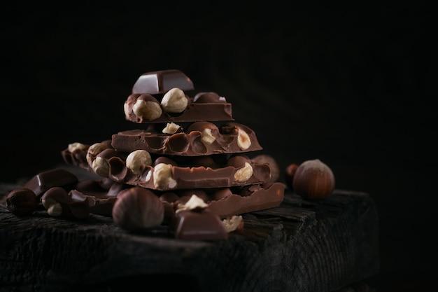 Stapel hazelnoot melkchocolade en noten op donkere houten achtergrond