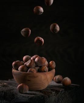 Stapel hazelnoten hazelnoot in een houten kom op een donkere houten achtergrond. vliegende noten in hun schelpen.