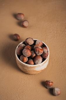 Stapel hazelnoten hazelnoot in een kom op een bruine achtergrond. verse noten in hun schelpen.