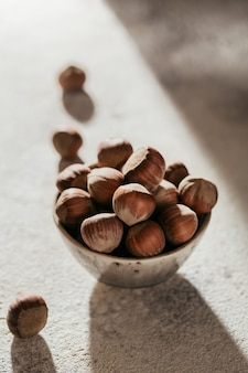 Stapel hazelnoten hazelnoot in een kom op een witte achtergrond. verse noten in hun schelpen.