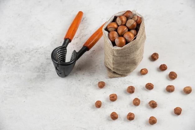 Stapel hazelnoten in jute met notenkraker op marmeren tafel.