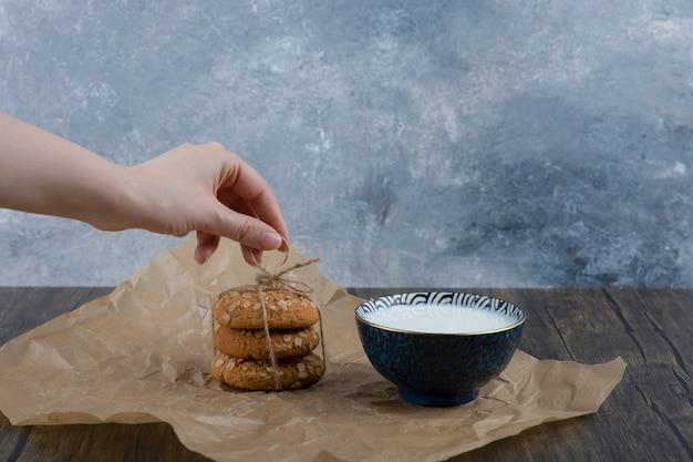 Stapel heerlijke koekjes met granen en een kom verse melk.