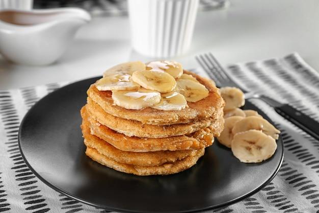 Stapel heerlijke kokos pannenkoeken met zoete saus en gesneden banaan op plaat, close-up