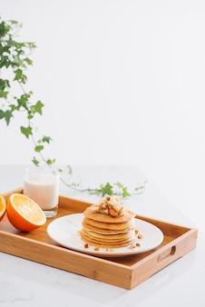 Stapel heerlijke pannenkoeken met chocolade, honing, noten en plakjes banaan op bord en servet