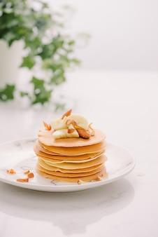 Stapel heerlijke pannenkoeken met chocolade, honing, noten en plakjes banaan op plaat
