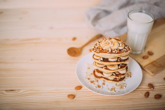 Stapel heerlijke pannenkoeken met honing, noten en plakjes banaan.