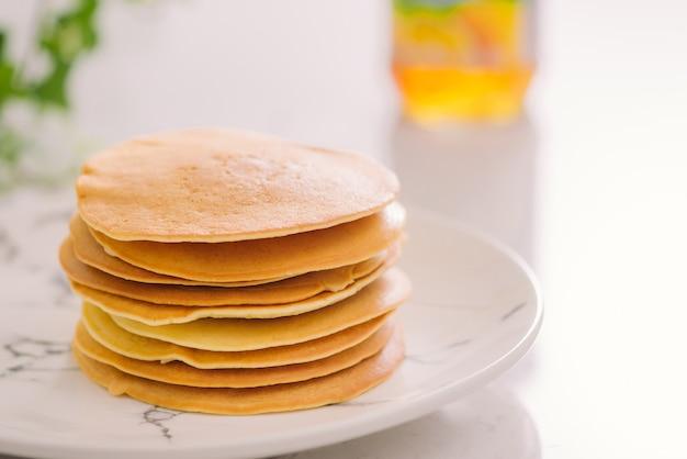 Stapel heerlijke pannenkoeken op plaat geïsoleerd op white