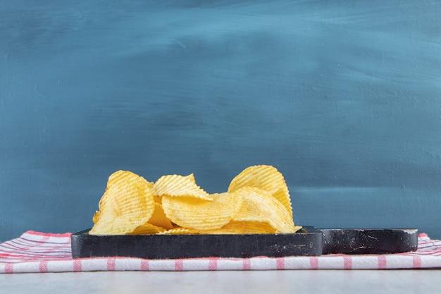 Stapel heerlijke rimpel chips op zwarte snijplank.