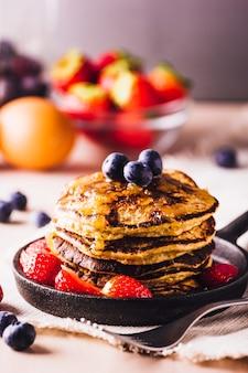 Stapel huisgemaakte pannenkoeken met bosbessen en aardbeien, perfect voor het ontbijt