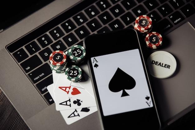 Stapel ð ips, smartphone en speelkaarten op keaboard. bovenaanzicht. online casino concept