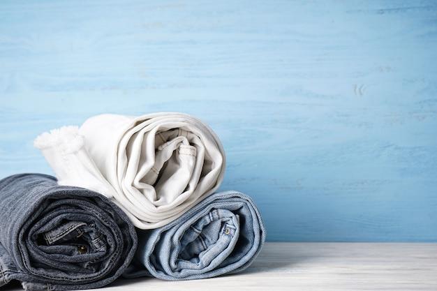 Stapel jeans van verschillende tinten, plaats voor tekst. jeans zijn gestapeld op een houten achtergrond.