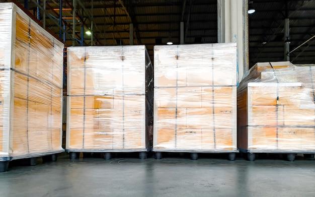 Stapel kartonnen dozen die plastic op pallets verpakken voor exportzending, logistiek in de magazijnindustrie, vrachtvervoer