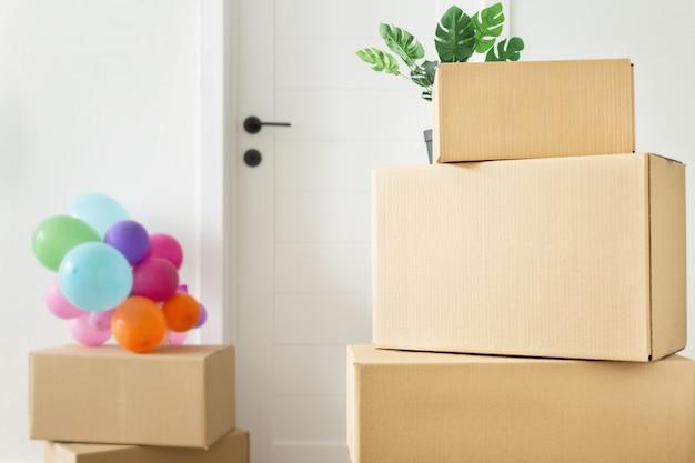 Stapel kartonnen dozen in de woonkamer. verhuizen naar een nieuw huisconcept