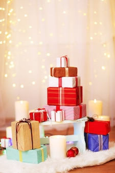 Stapel kerstcadeaudozen op houten kruk, op lichte achtergrond