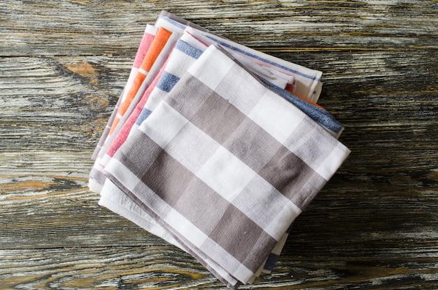 Stapel keukenhanddoeken of servetten over de rustieke houten lijst.
