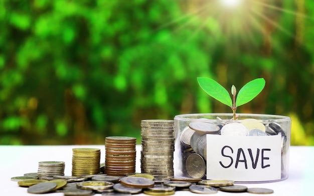 Stapel klaar muntstukken en bewaar berichten in een zilveren kruik op een vage groene achtergrond.