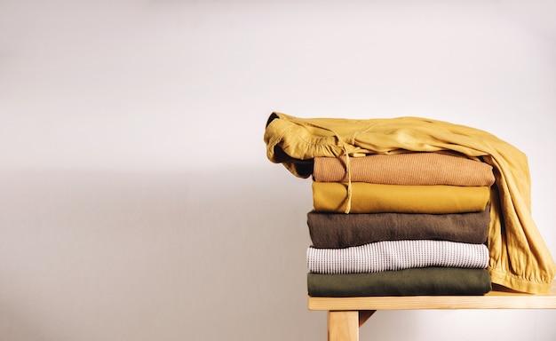 Stapel kleding op houten bank bij de witte muur