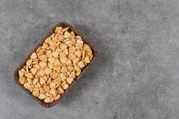 Stapel kleine koekjes in mand over grijze tafel.