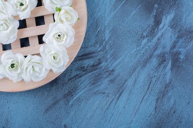 Stapel kleine witte bloemen geplaatst op blauw.