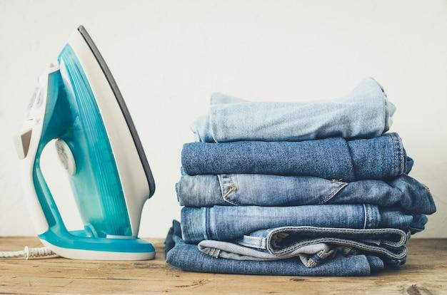 Stapel kleren en strijkijzer op de tafel
