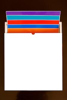 Stapel kleurrijke 12 x 12 vellen zelfklevend papier geïsoleerd op de witte achtergrond. gesorteerde kleuren.