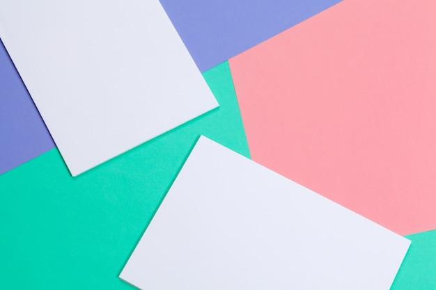 Stapel kleurrijke en witte blanco vellen papier voor uw ontwerp, bovenaanzicht plat lag