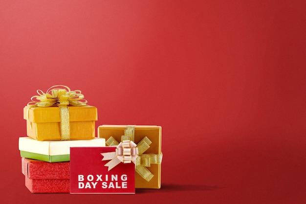 Stapel kleurrijke geschenkdoos met lint en tweede kerstdag verkoop tekst op een rode achtergrond