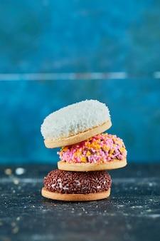 Stapel kleurrijke gezwollen koekjes op blauwe muur.