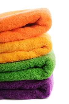 Stapel kleurrijke handdoeken die op wit worden geïsoleerd