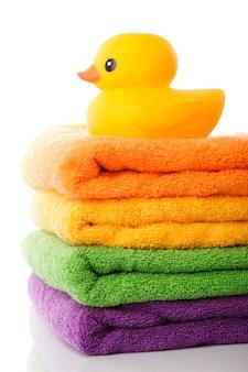 Stapel kleurrijke handdoeken en gele rubberen eend op wit wordt geïsoleerd
