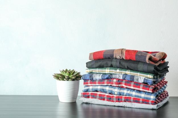 Stapel kleurrijke shirts en vetplant op tafel tegen lichte achtergrond