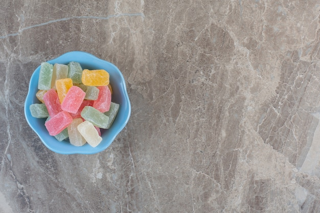 Stapel kleurrijke snoepjes in blauwe kom. bovenaanzicht over grijze achtergrond.