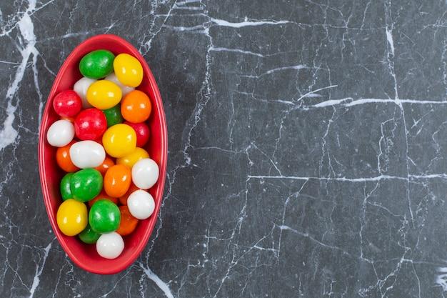 Stapel kleurrijke snoepjes in rode kom