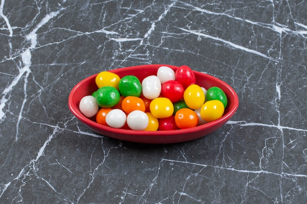 Stapel kleurrijke snoepjes in rode kom.