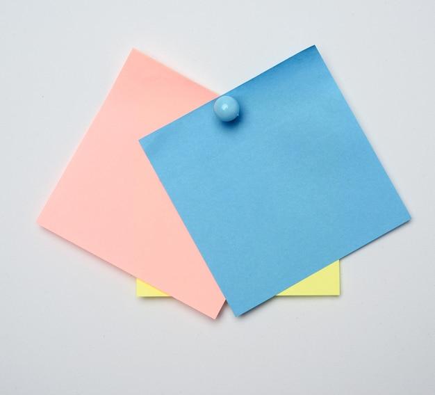 Stapel kleurrijke stickers vastgemaakt door blauwe knop