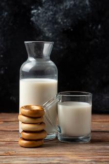 Stapel koekjes, een fles melk en een glas melk op houten lijst.