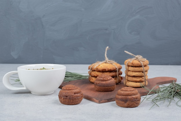 Stapel koekjes gebonden met touw en kopje thee op grijze achtergrond.
