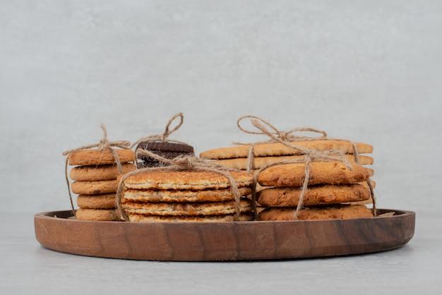 Stapel koekjes gebonden met touw op houten plaat.