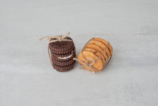 Stapel koekjes gebonden met touw op witte tafel.