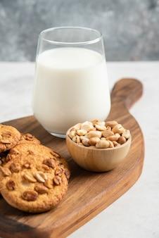 Stapel koekjes met honing, melk en pinda's op een houten bord.