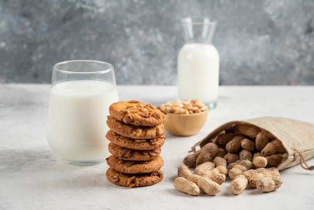 Stapel koekjes met honing, melk en pinda's op marmeren tafel.